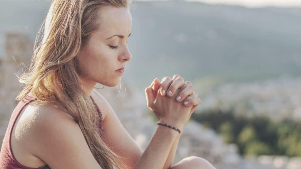 young woman praying top of mountain