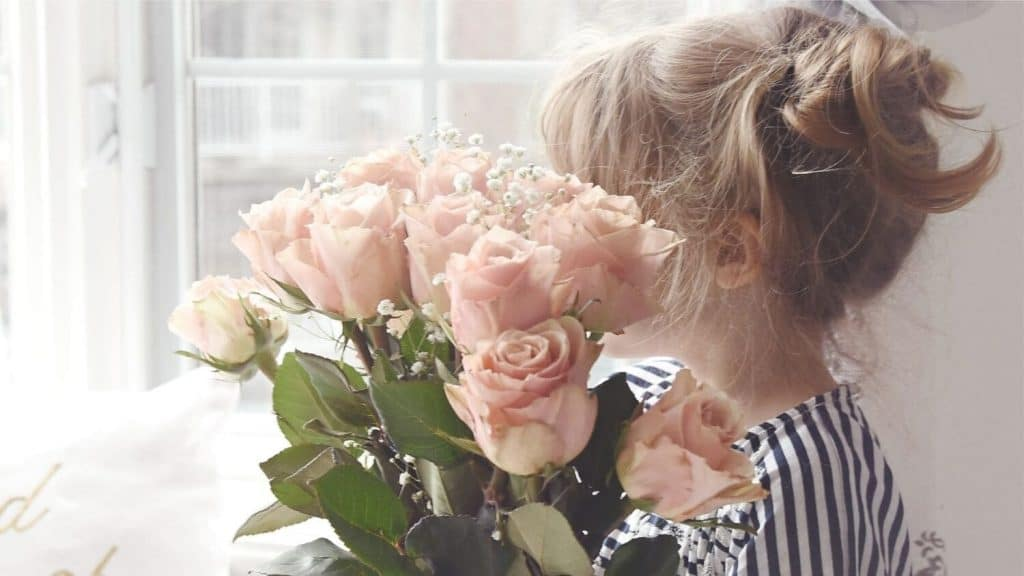 woman holding bouquet of roses covering face