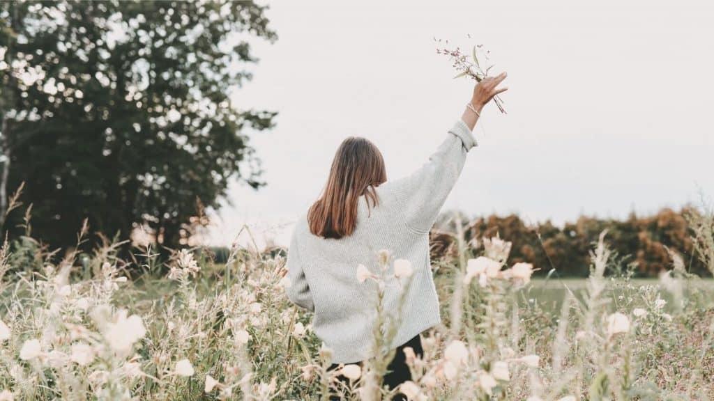 woman walking in meadow holding up wildflowers