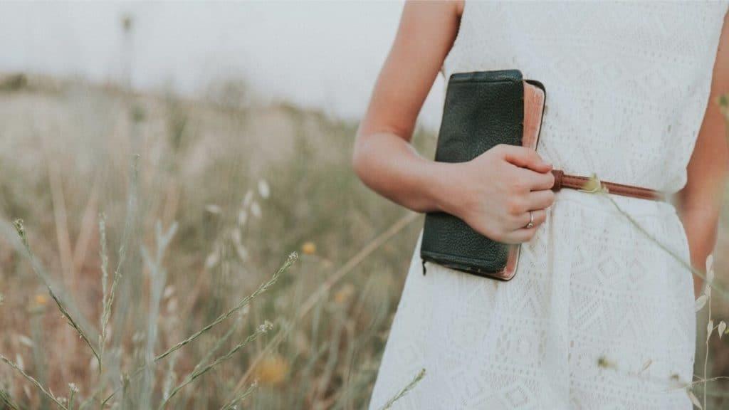 woman carrying Bible meadow