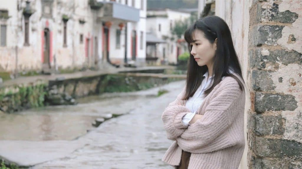 young woman leaning on wall outside