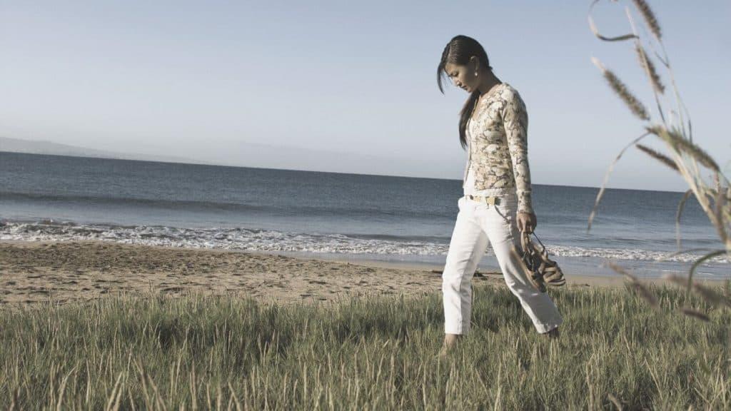woman walking in grass on beach