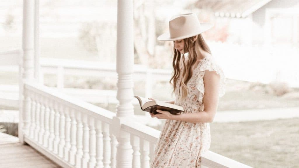 woman wearing hat leaning on porch railing reading a book