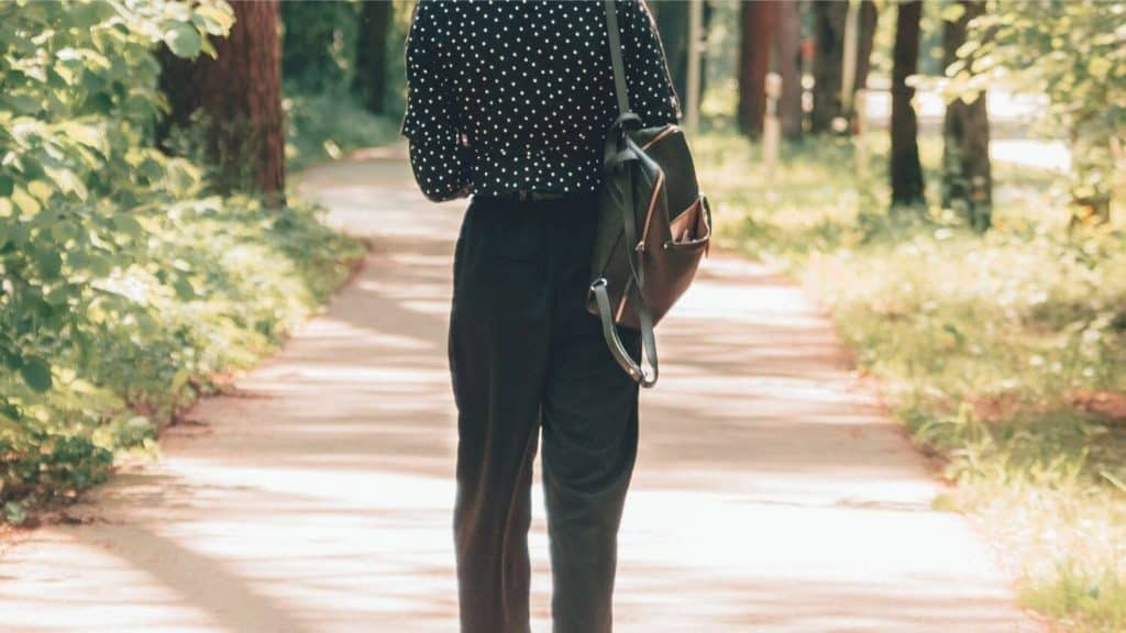woman wearing pants walking park path