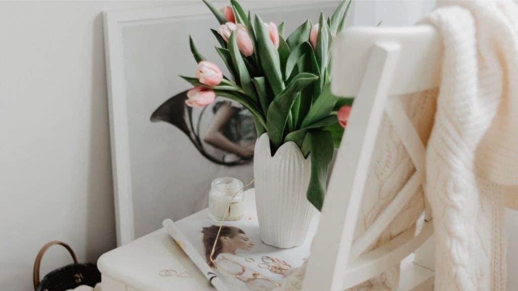 vase of tulips in wooden chair