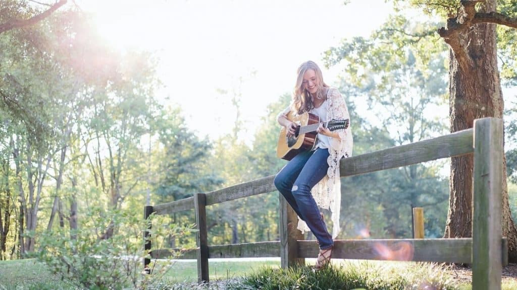 girl sitting on wood rail fence playing a guitar