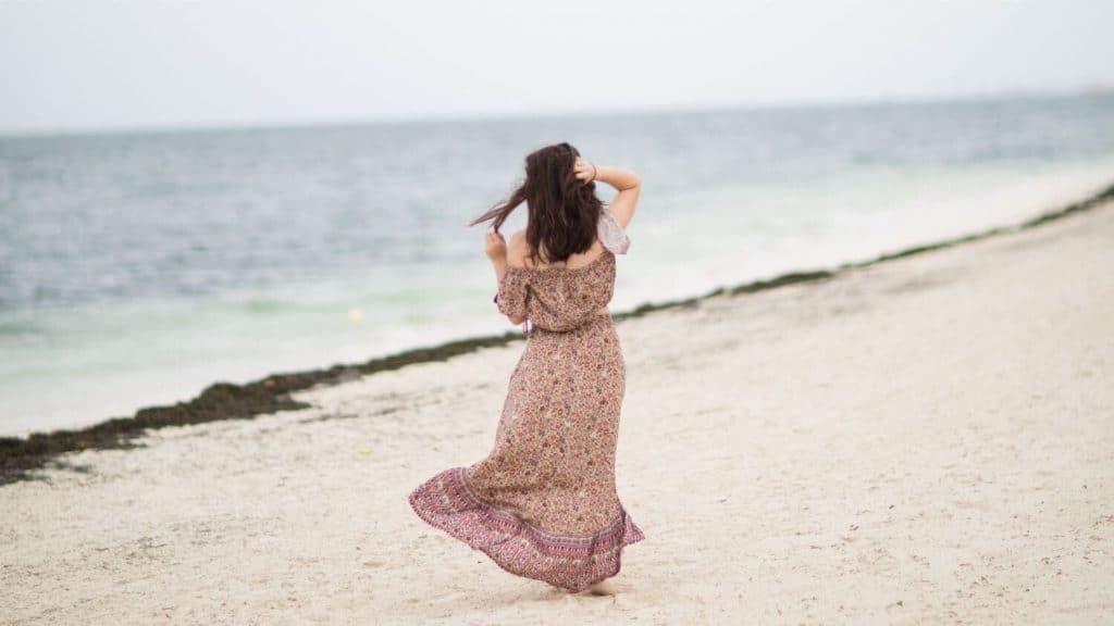 woman in long dress walking on beach windy day