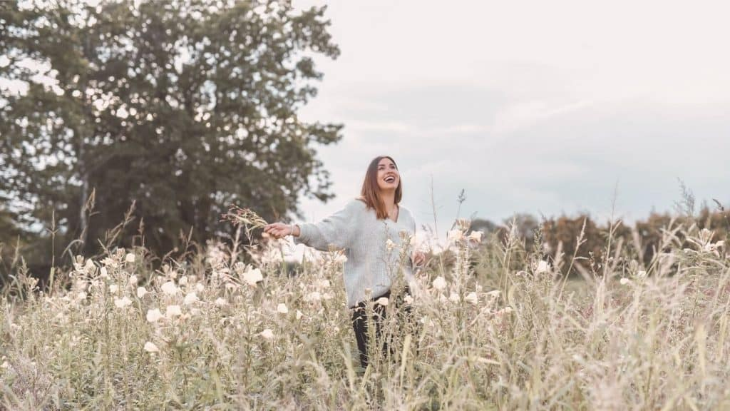 woman smiling arms wide meadow