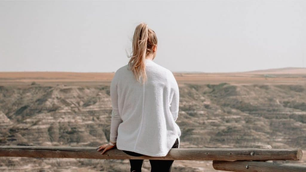 girl sitting on wood rail fence canyon