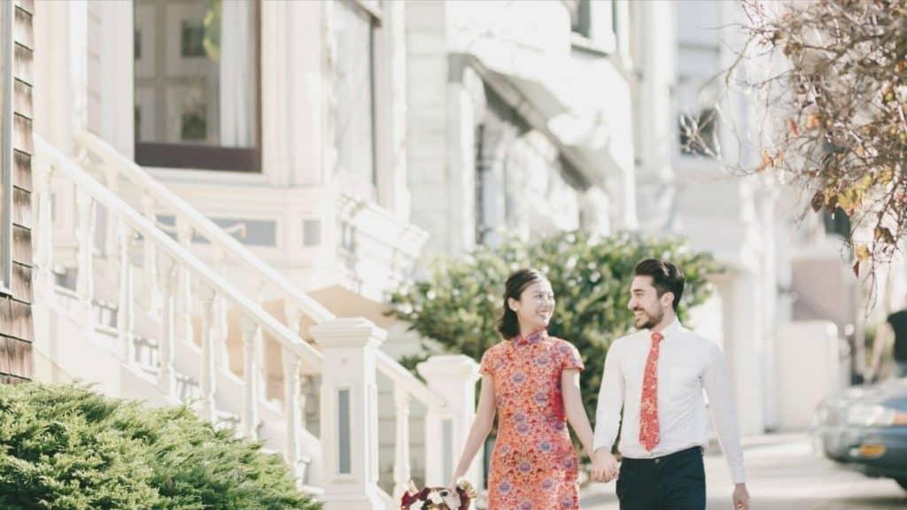 couple walking city sidewalk holding hands