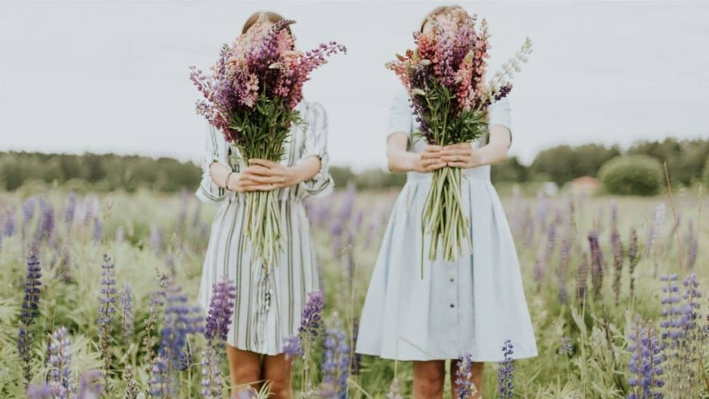 two girls holding bouquet covering faces
