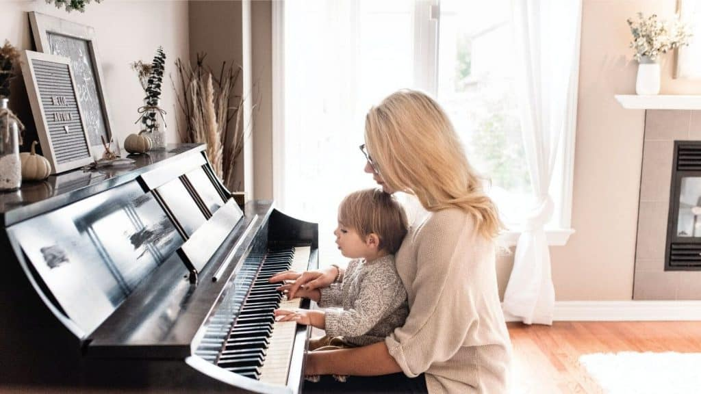 mom holding toddler playing piano