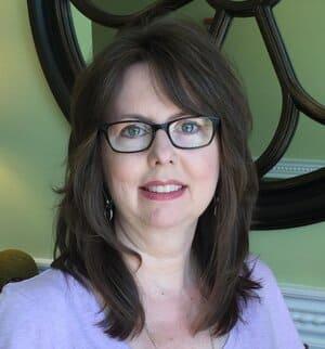 Teresa Hodge pink shirt glasses mirror behind